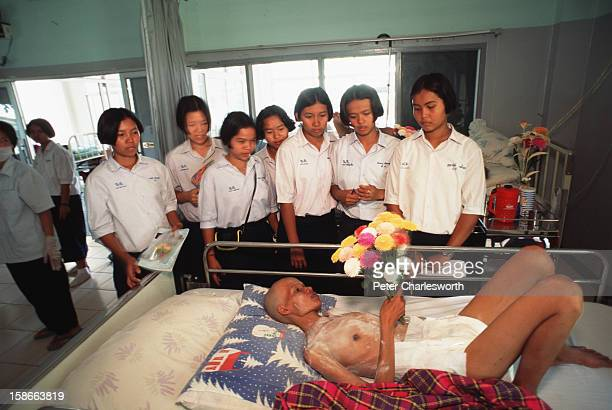 Schoolchildren on a trip to learn about AIDS talk with a patient with full blown AIDS who is lying in a bed in the hospital at the Buddhist Temple...