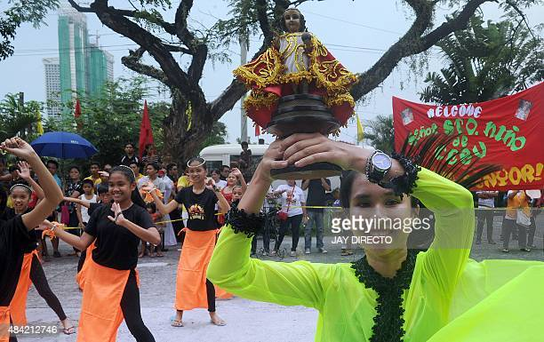Schoolchildren perform the sinulog dance while holding religious icons to welcome the historical statue of Santo Nino or baby Jesus brought from Cebu...