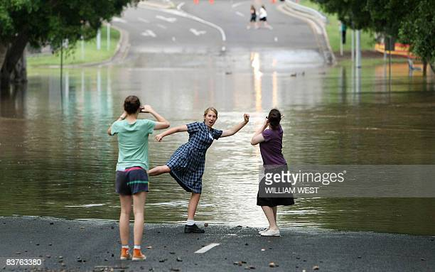 Schoolchildren play in front of a road flooded by the Bremer River in central Ipswich some 50 kilometres west of Brisbane on November 20 2008 as...