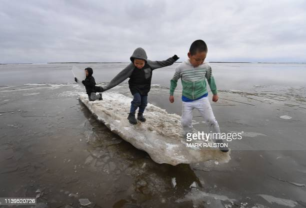 Schoolchildren play on melting ice at the climate change affected Yupik Eskimo village of Napakiak on the Yukon Delta in Alaska on April 18, 2019. -...
