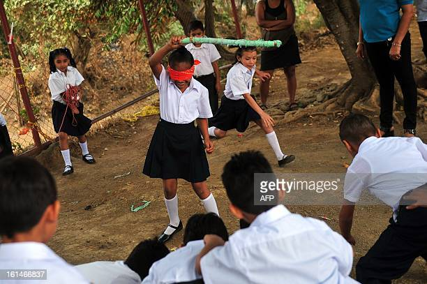 Schoolchildren play to break the 'pinata' in the yard of the Jean Paul Genie primary school during the year's first day of classes in Managua on...