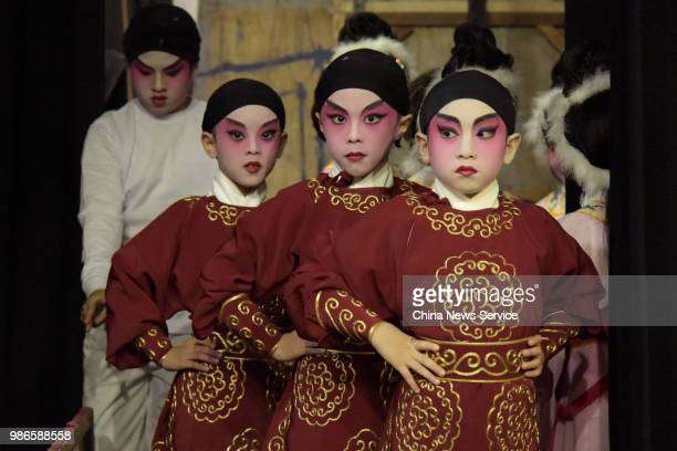 Schoolchildren prepare backstage prior to a Cantonese opera performance on June 26 2018 in Hong Kong China Thirtyfour children from Po Leung Kuk...