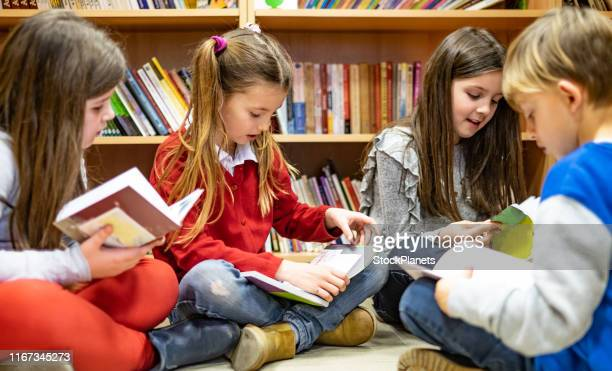 schoolchildren reading a books - reading stock pictures, royalty-free photos & images