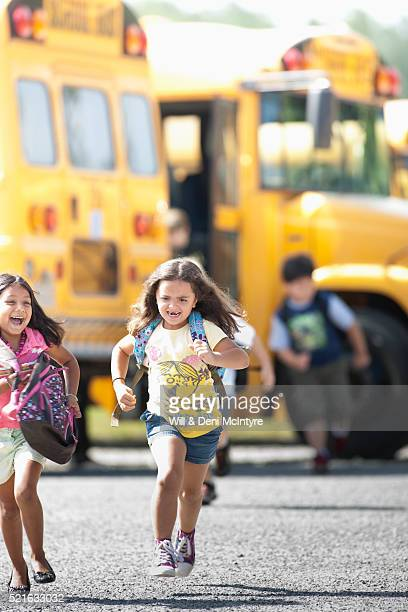 Schoolchildren running near school bus