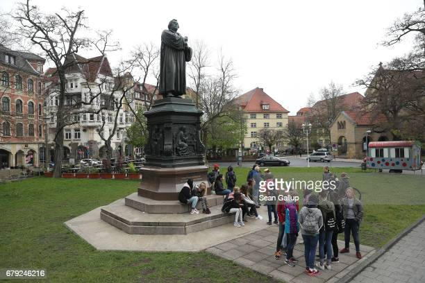 Schoolchildren stand next to a statue of Martin Luther whose 95 theses of 1517 set in motion the Reformation in the city center on May 5 2017 in...