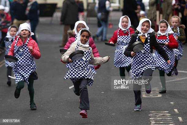 Schoolchildren take part in a pancake race ahead of the annual Shrove Tuesday ladies transAtlantic pancake race on February 9 2016 in Olney England...