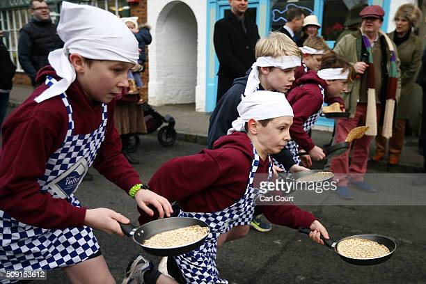 Schoolchildren take part in a pancake race on February 9 2016 in Olney England On Shrove Tuesday every year the ladies of Olney Buckinghamshire...