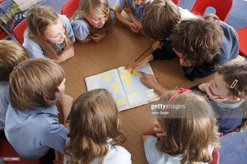 schoolchildren using atlas together at school : Stock Photo