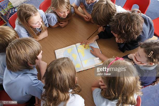 schoolchildren using atlas together at school