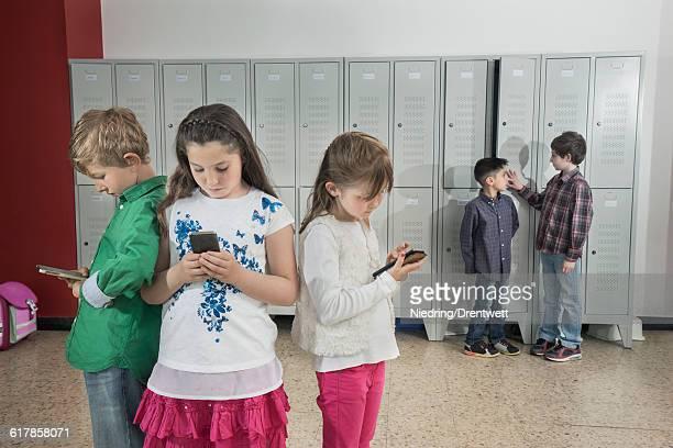 'Schoolchildren using smartphone in corridor near lockers, Bavaria, Germany'