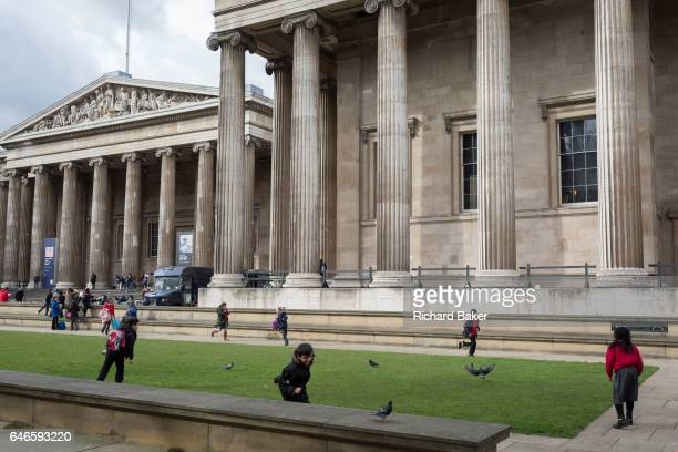 Schoolchildren visiting the British Museum run around on the grass and bother pigeons on 28th February 2017 in London England