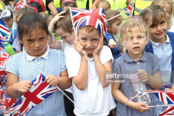 Schoolchildren wait to see Prince Charles Prince Of Wales and Camilla Duchess Of Cornwall as they attend the Fowey Festival Celebration during day...