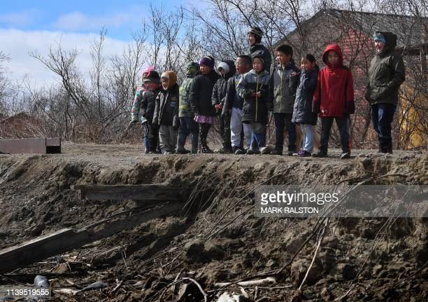 Schoolchildren walk beside severe erosion of the permafrost tundra next to their school at the climate change affected Yupik Eskimo village of...