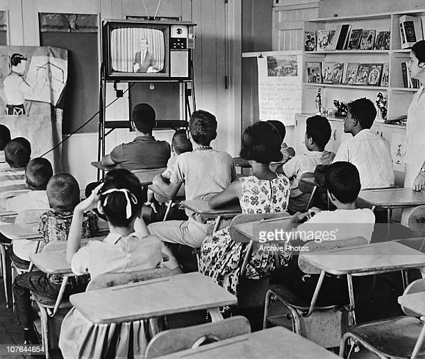 Schoolchildren watching a TV programme in their classroom as a teacher looks on, circa 1963.