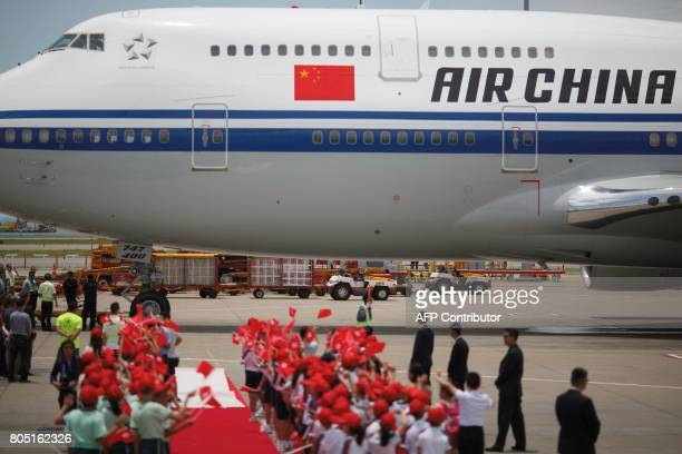 Schoolchildren wave Hong Kong and China flags as the Air China Boeing 747400 aircraft transporting China's President Xi Jinping pulls out for...