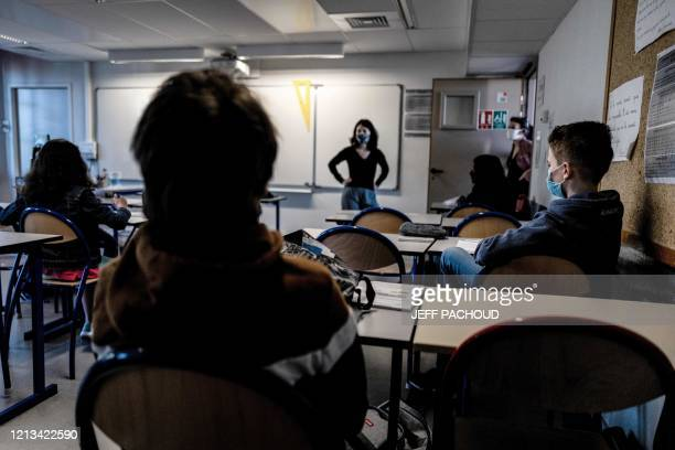 Schoolchildren wearing protective face masks attend a lesson in a middle school classroom, on May 18, 2020 in Lyon, central eastern France, after...