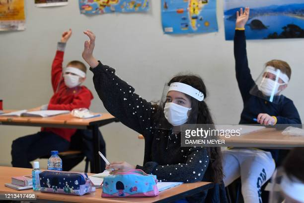 Schoolchildren wearing protective mouth masks and face shields attend a course in a classroom at Claude Debussy college in Angers, western France, on...