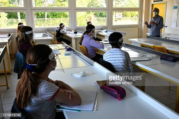 Schoolchildren wearing protective mouth masks and face shields listen to their teacher in a classroom at Claude Debussy college in Angers western...
