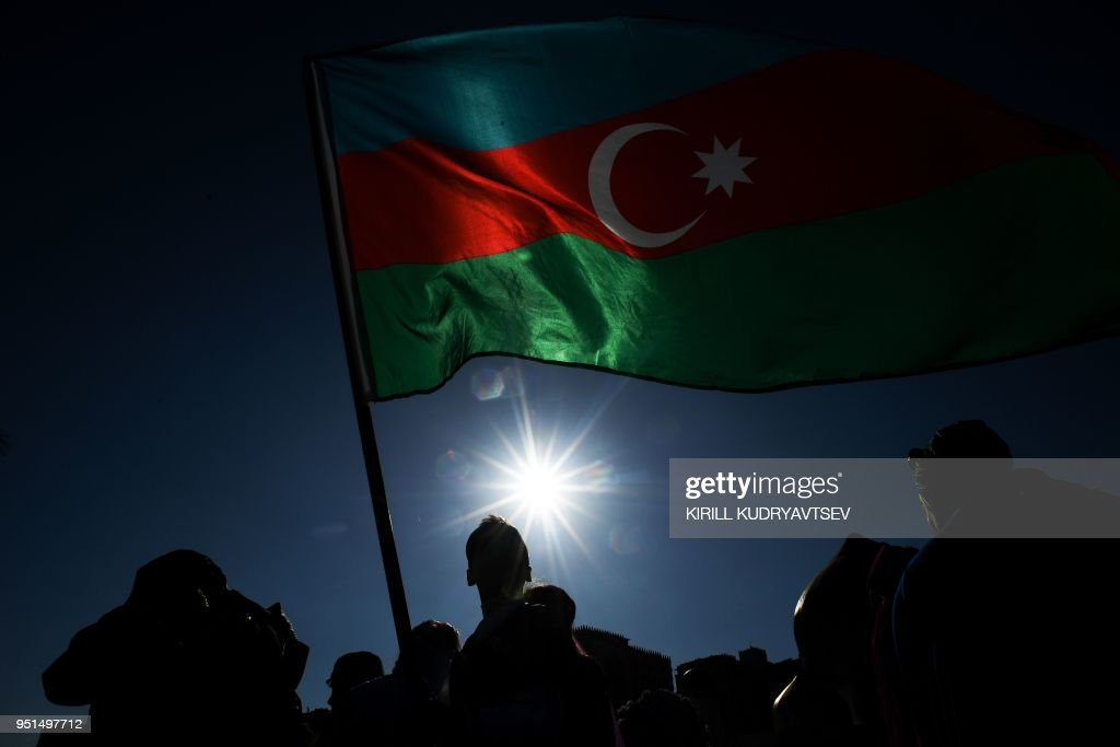 TOPSHOT - Schoolchildren wearing traditional dresses wave an Azerbaijani flag during the annual Day of Reading event outside the Heydar Aliyev Cultural Center in Baku on April 26, 2018, ahead of the Formula One Azerbaijan Grand Prix. - Participants from 40 schools of Baku took part in the event.