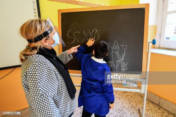 Schoolchildren with mental disabilities such as autism or mental retardation are helped by their teachers in a classroom with social distancing...