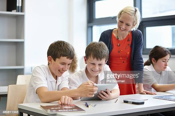 Schoolchildren working in class with teacher