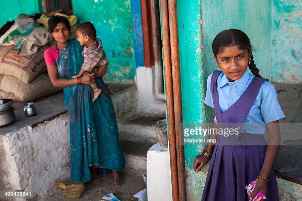 Schoolgirl and a mother holding her baby at the doorstep of a house in the peaceful village of Aihole in Karnataka, India.