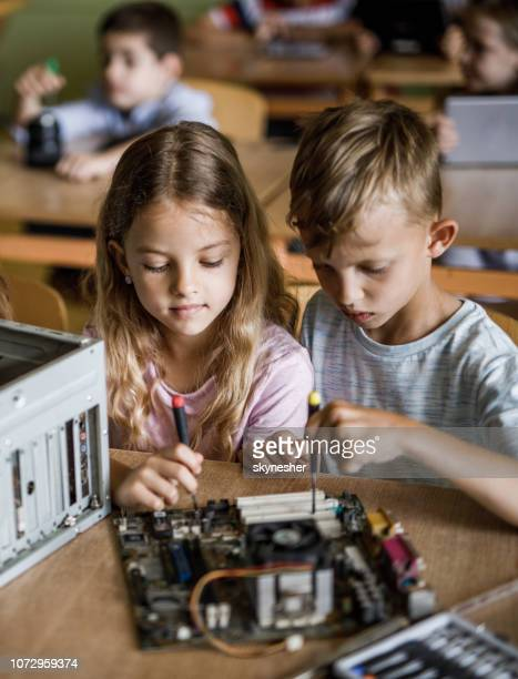 schoolgirl and her classmate repairing computer mother board during a class in the classroom. - stem topic stock pictures, royalty-free photos & images