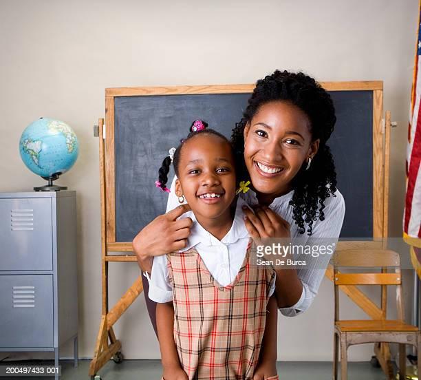 Schoolgirl (5-7) and teacher smiling, portrait