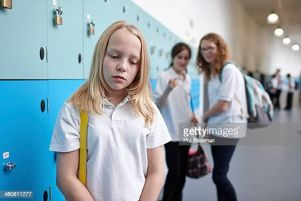 schoolgirl being bullied in school corridor - bullying escolar fotografías e imágenes de stock