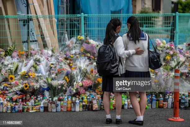 Schoolgirl comforts her friend as they pause next to flowers and tributes laid at the scene of a knife attack on a group of schoolchildren, on May...