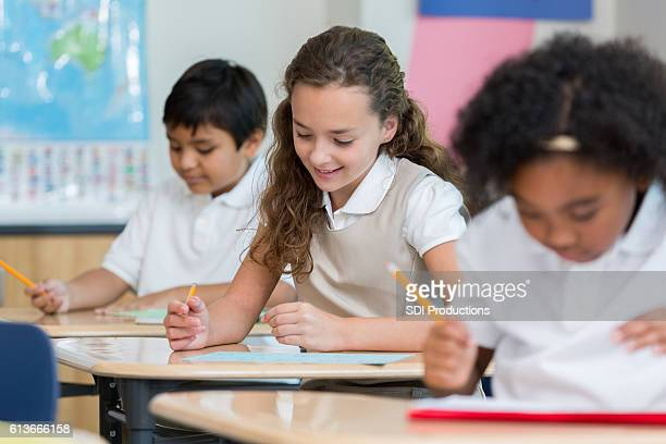 Schoolgirl concentrates while taking test