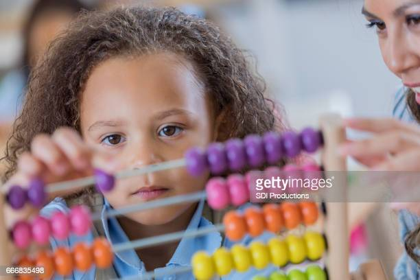 Schoolgirl concentrates while using an abacus during math class