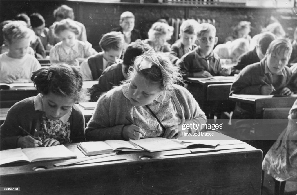 A schoolgirl copies notes from her friend's book in a classroom of Walsgrave Colliery School, near Coventry. The increased birthrate following World War II has led to overcrowding in schools, and classes of up to fifty children. Original Publication: Picture Post - 9109 - Overcrowded Schools - unpub.