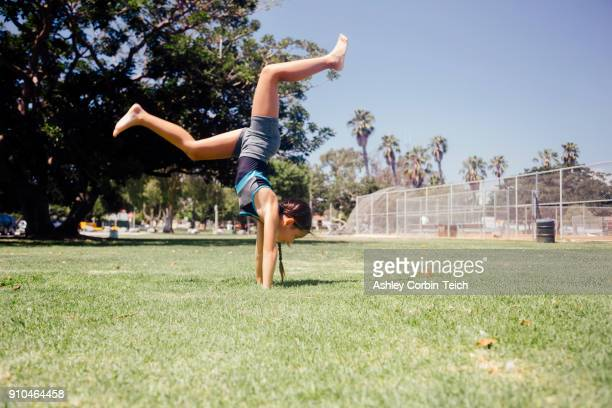 schoolgirl doing cartwheel on school sports field - cartwheel stock pictures, royalty-free photos & images