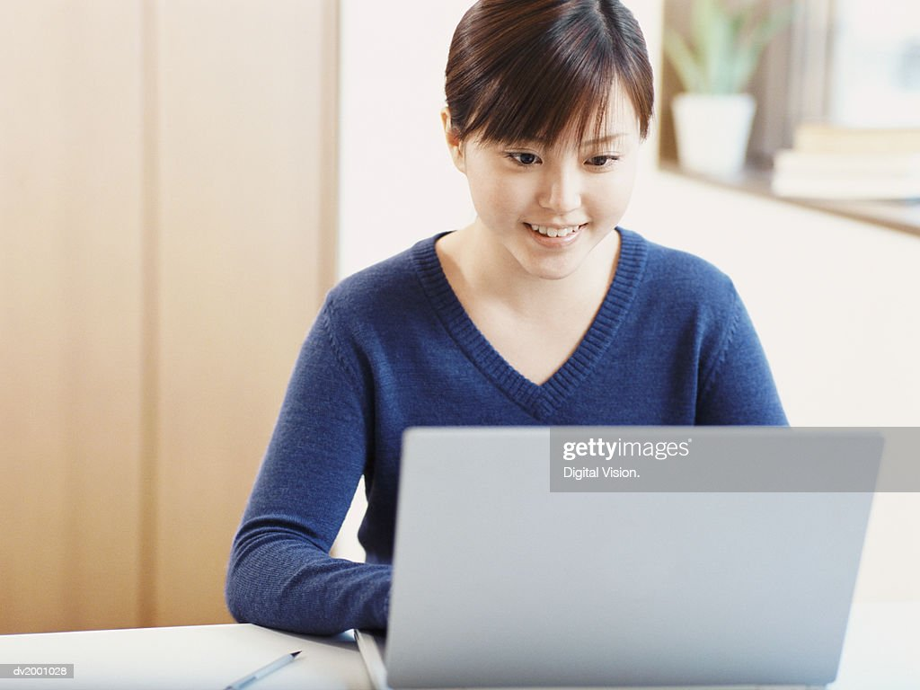 Schoolgirl Doing Her Homework on Her Laptop : Stock Photo