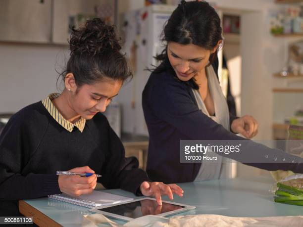 schoolgirl doing homework on ipad, mum looking on - home schooling stock pictures, royalty-free photos & images