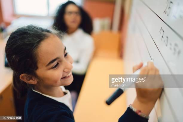 Schoolmeisje doen wiskunde op whiteboard