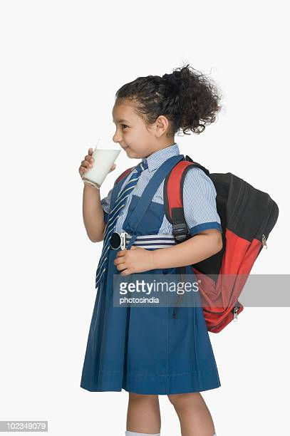 Schoolgirl drinking a glass of milk and carrying a schoolbag