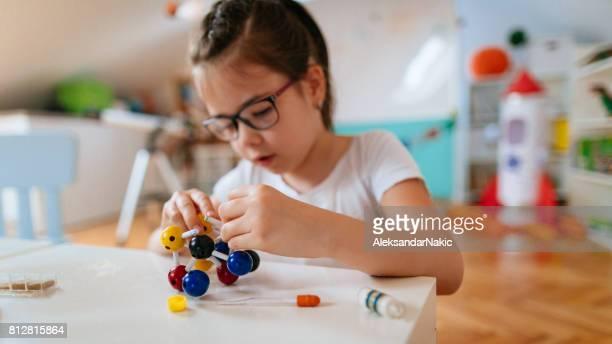 Schoolgirl examining molecule model