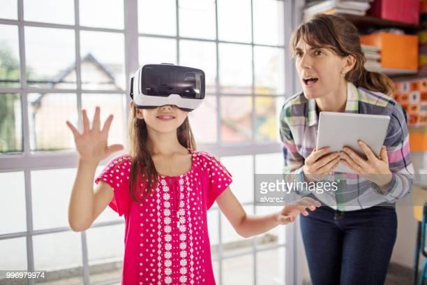 Schoolgirl experiencing virtual reality by teacher
