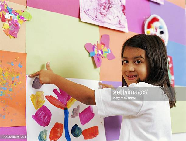 schoolgirl (5-7) fixing painting to wall display, smiling, portrait - kids art stock pictures, royalty-free photos & images