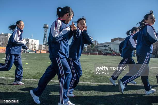 A schoolgirl gestures and others laugh as they jog around the school sports field during a physical education class at Tokyo Korean Junior and Senior...