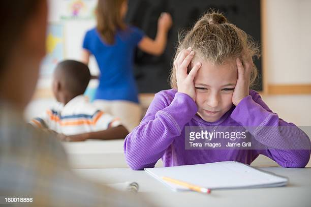Schoolgirl (8-9) having problems while learning in classroom
