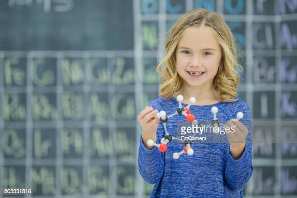schoolgirl holding molecule model - periodic table stock photos and pictures