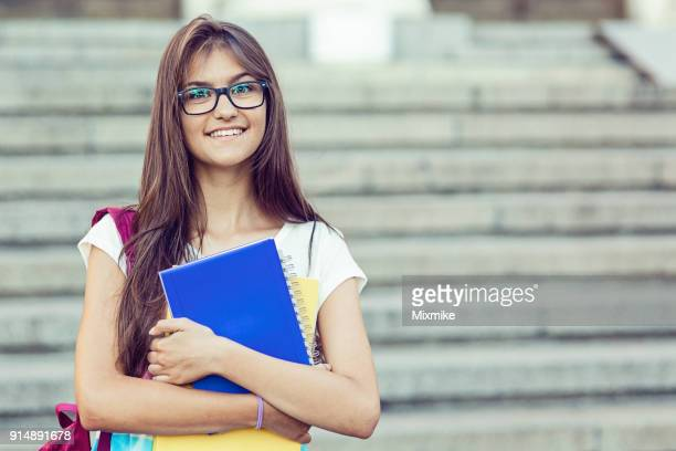 schoolgirl holding textbooks and smiling at camera - 18 19 years stock pictures, royalty-free photos & images
