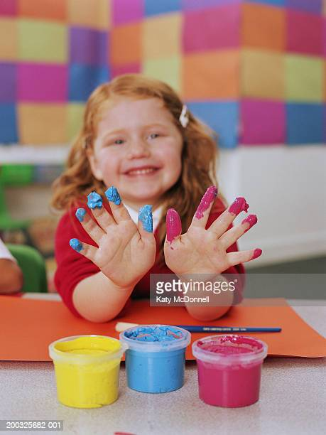 Schoolgirl (4-6) holding up paint covered fingers, smiling, portrait