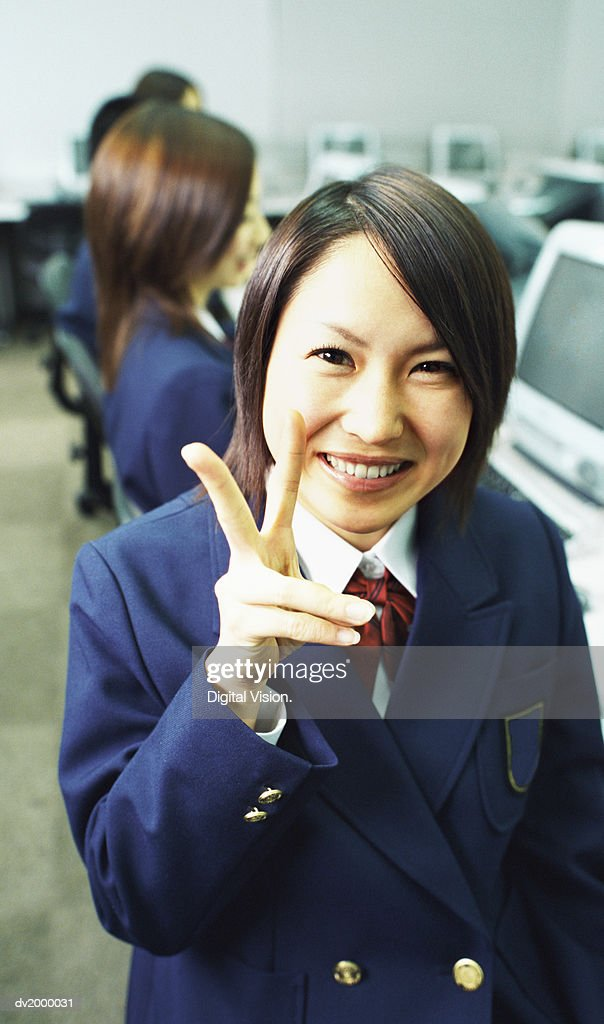 Schoolgirl in a Computer Room Making a Peace Sign Gesture to the Camera : Stock Photo