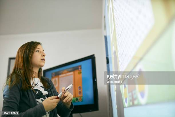 Schoolgirl in class looking at interactive whiteboard