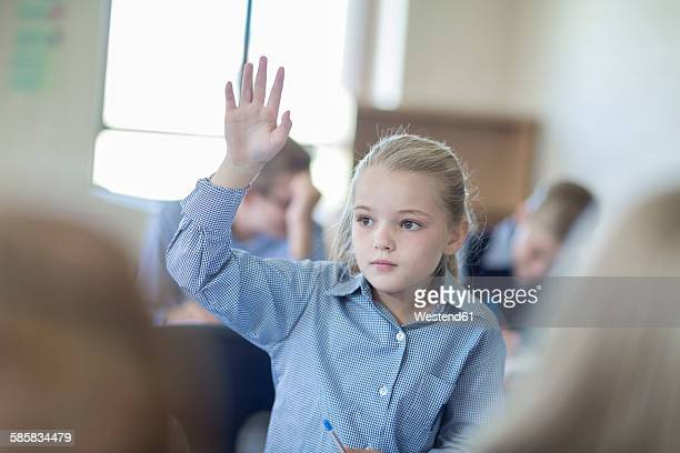 schoolgirl in classroom raising her hand - one girl only stock pictures, royalty-free photos & images