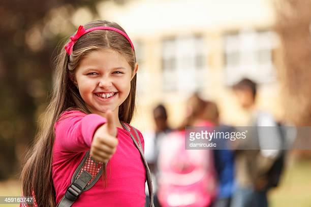 Schoolgirl in front of the school showing thumb-up